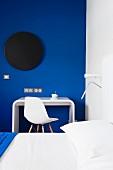 Farbstyling im Schlafzimmer mit Designer Schreibplatz und Klassikerstuhl vor königsblau getönter Wand mit schwarzer Scheibe