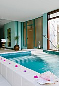 Wellness pool decorated with flowers and shells, turquoise walls in a spa area