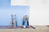 Man painting a wall blue