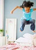 Auf einem Bett fröhlich hüpfendes Mädchen