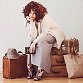 Fashionably dressed young woman sitting, waiting, on suitcases