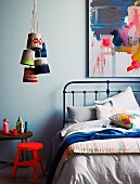 Neon-red stool, retro metal bed and bunch of pendant lamps with dip-dyed knitted lampshades hanging from ceiling