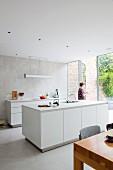 Reduzierte weiße Designerküche mit gefliester Wand und geöffneter Glasfront zur Terrasse mit hoher Backstein-Gartenmauer