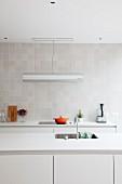 Reduzierte weiße Designerküche mit grau-weiß gefliester Wand und Designer-Arbeitsleuchte