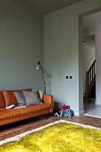 Hellgrüner Wolleppich, pastellgrüne Wandfarbe, gemütliches cognacfarbenes Ledersofa mit Kissen und Stehlampe in Wohnzimmerecke