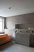 Designerbad mit Holzbadewanne, Betonwaschtisch, Vorsatzschale und Wandausschnitt in reduziertem Stil
