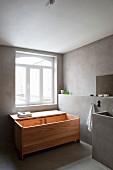 Designerbadewanne aus Holz mit offenem Deckel vor restauriertem Badfenster, seitliche Wand mit Vorsatzschale und Waschtisch in Betonausführung