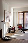 Wohnzimmerecke mit Lounge Chair und passendem Fussschemel auf hellem Teppich, dahinter Jalousie an Balkontür, im Vordergrund Holzschale auf Boden vor offenem Kamin