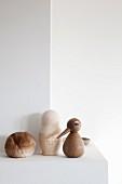 Verschiedene Figuren aus Holz, Keramik und Fell auf Konsole an Wand