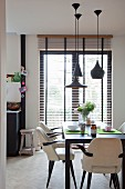 Chairs covered in white leather at black dining table set for breakfast below designer pendant lamps; balcony doors with louver blinds in background
