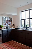 Bright, striped rug in front of L-shaped kitchen counter with black wooden drawer fronts in modern kitchen