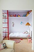 Partially visible armchair in front of red ladder, standard lamp with pleated lampshade next to bed and books and soft toys on high encircling shelf