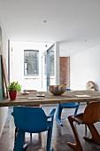 Verschiedenfarbige Retro- Schalenstühle vor rustikalem Küchentisch mit heller Holzplatte, im Hintergrund Blick in kleinen Patio