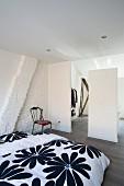 Geblümte Bettwäsche auf schlichtem Bett im Dachzimmer, weisse Raumteiler vor offener Ankleide mit minimalistischem Flair