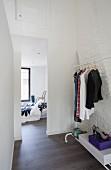 Mobiler Kleiderständer mit Schuhablage vor geweisselter Ziegelwand, Blick durch raumhohen Durchgang auf Bett am Fenster