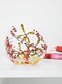 Flower arrangement of orchids & pink pepper berries in spherical vase