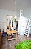 White-painted loft bed with ship ladder stairs, laptop on desk and green, faux fur rug on unpainted wooden floor