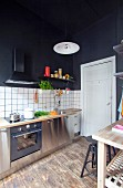 Kitchen counter with white, tiled splashback and black-painted walls and ceiling in renovated period apartment