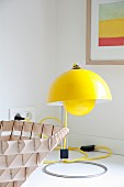 Yellow, retro-style designer table lamp with yellow power cord on white surface