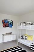 Kinderzimmer mit weißem Etagenbett, schwarz-weißen Zickzackmuster Kissen und gestreiftem Teppich