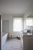 Hellgrau gefliestes reduziertes Bad mit weißer Badewanne und Doppelwaschbecken, Jalousie vor dem Fenster und Teppichläufer vor Waschbeckenunterschrank