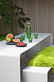 Fresh fruit and drink in green bottle with matching glasses on white table and bench with green sheepskin blanket on terrace