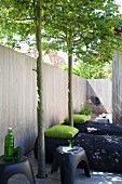 Black floor-cushion loungers with green pillows and plastic stools on terrace with wooden fence