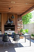 Black shell chairs with delicate metal frames at long table on roofed terrace with fireplace and firewood stacked against wooden wall in courtyard