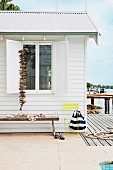 White beach cottage decorated with shells and drift wood; a long wooden bench along the side of the wall