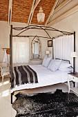 Himmel-Doppelbett mit gestreiftem braunen Plaid und Dachkonstruktion mit Bambusdecke