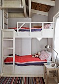 Hand-crafted bunk bed with ladder and retro, stainless steel table lamp on bedside table in wood-clad room