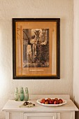 Fruit dish on white cabinet, old framed photo on wall in corner of room