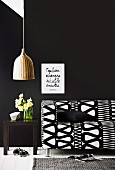 Sofa with black and white geometric cover against black wall and pendant lamp with wicker lampshade