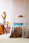 Blonde woman standing at console table next to double bed with airy curtains attached to suspended rods