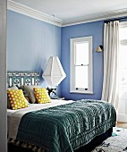 Double bed with quilt, yellow dotted pillows and ethnic pattern on bed head against pastel blue wall