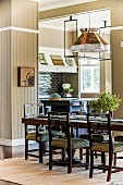 Upholstered chairs at long, dark wooden table below pedant lamps with traditional fabric lampshade in wood-clad kitchen painted pale brown