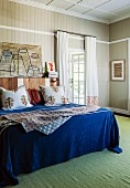 Double bed with blue bedspread and scatter cushions against wood-clad wall and green rug in bedroom