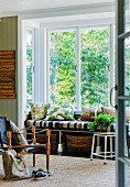 Armchair with black leather seat and carved wooden frame opposite window with window seat and view of garden