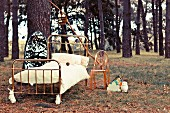 Fairytale: metal bed and a transparent chair in the forest