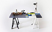 Contrast of industrial and modern styles - vintage accessories on grey half of table with stencilled numbers and Mondrian pattern in cool colours