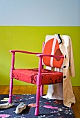 Chair in various shades of red on a floral patterned rug in front of a colorful wall