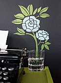 Painted, floral wall decoration and a water glass to an antique typewriter on a console table next