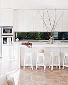 Modern kitchen in white with kitchen counter and bar stools