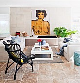 Living room with modern painting of a female nude and sitting area with sofas, coffee table and long, built in bench seat