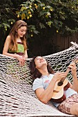 Young man lying in a hammock, playing a ukulele to his sister