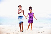 Two dark-skinned girls standing on beach hand in hand
