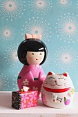Japanese doll money box, Oriental lucky cat and gift box against pale blue wallpaper