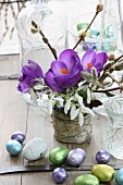 Spring posy of purple crocuses, snowdrops and willow catkins next to chocolate Easter eggs
