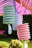 Paper lanterns of various colours hanging from parasol in garden