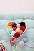 Pompoms of various colours in heart-shaped china dish